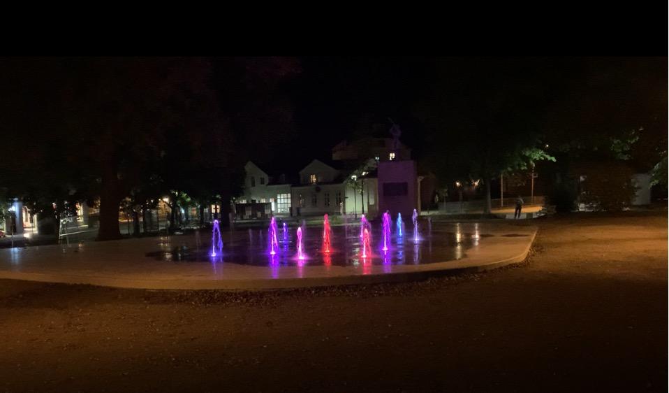 Belyste fontenedyser som spruter vann