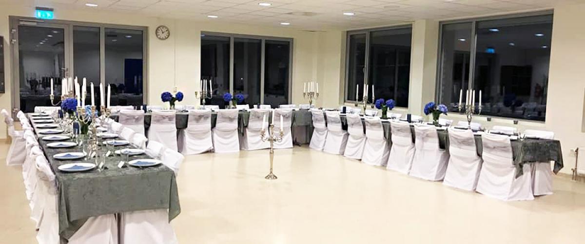 Selskapslokale med pent dekkede langbord