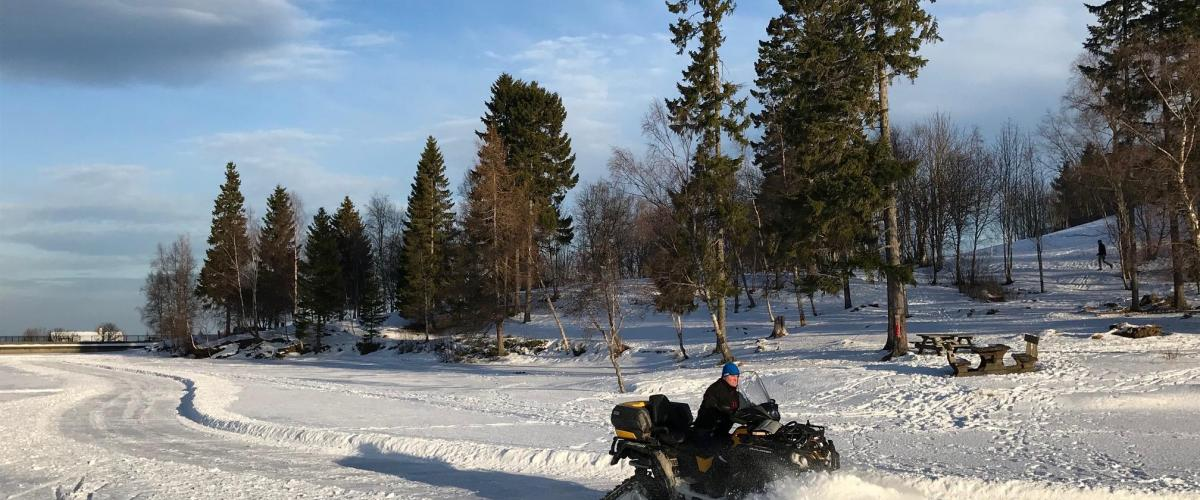 Brøyting av is med snøscooter på naturisbane