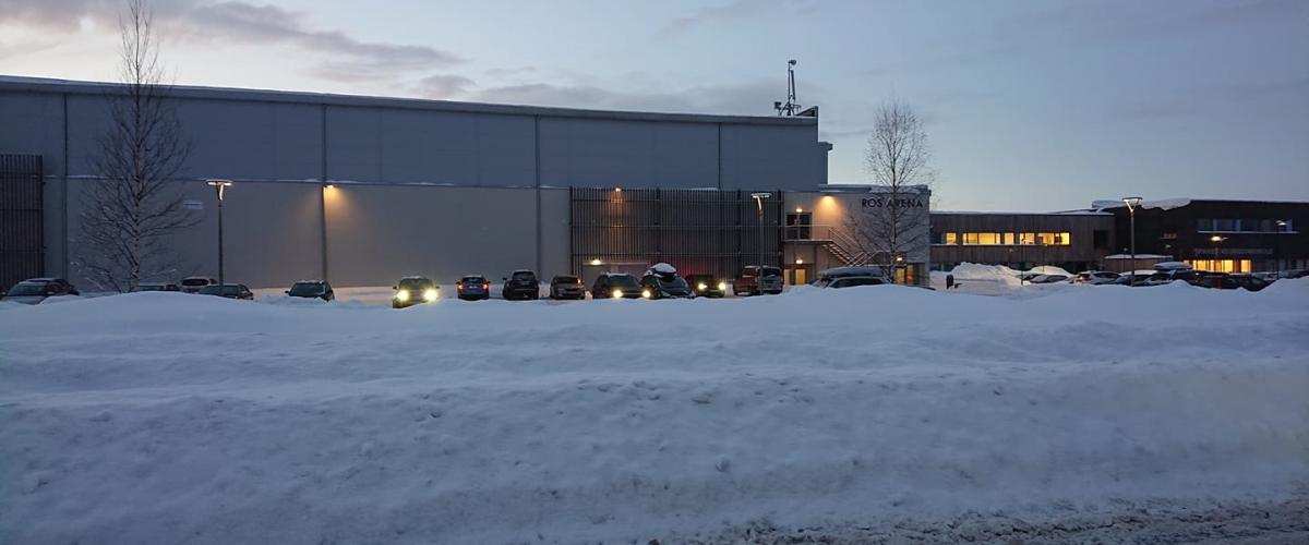 Utside av arena vinterstid, med biler på parkeringsplass