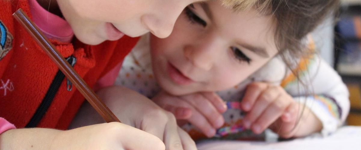 To barn fordypet i en skrivebok.