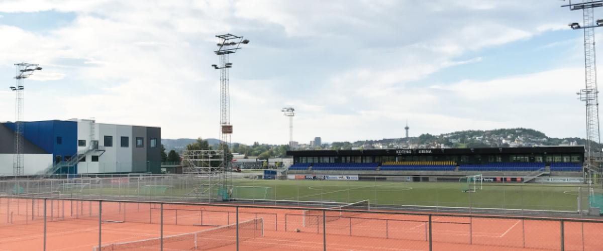 Utendørs tennisanlegg med Koteng Arena i bakgrunnen