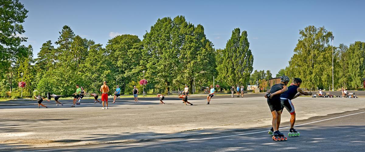 Flere mennesker i god fart på rulleskøyter rundt inlinebane en sommerdag