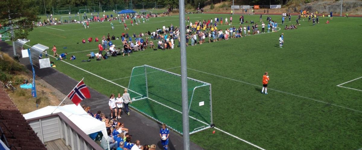 To 7'er kamper underveis på fotballbanen, med høyt antall tilskuere