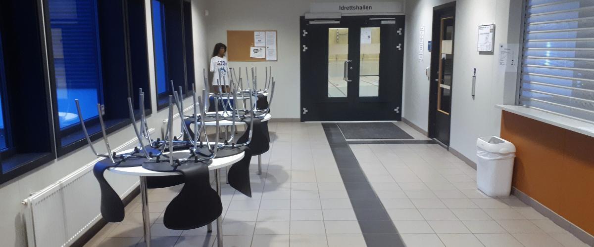 Inngangsparti med kiosk, sitteplasser og bord.