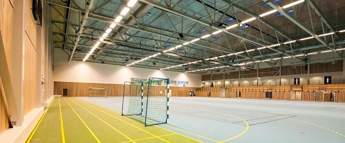 Innside av idrettshall, med løpe- og håndballbane