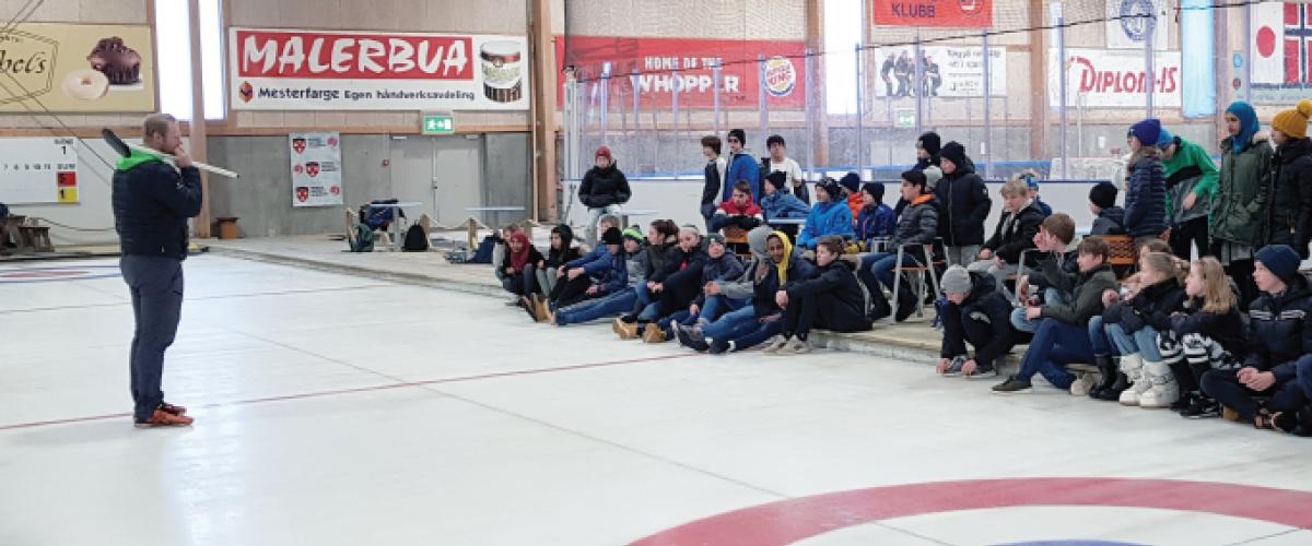 Ungdommen følger nøye med på curlingtrenerens instruksjoner
