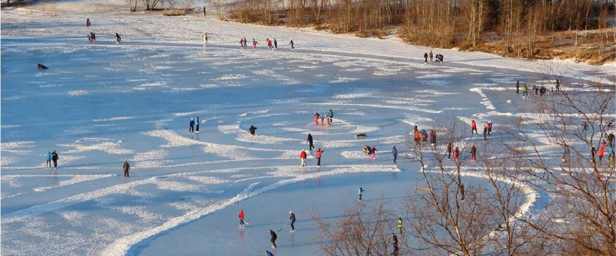 Stor aktivitet på naturisbane en solrik vinterdag