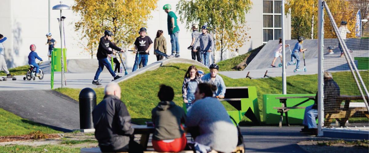 Rullepark med aktiv ungdom, samt voksne sittende på benker