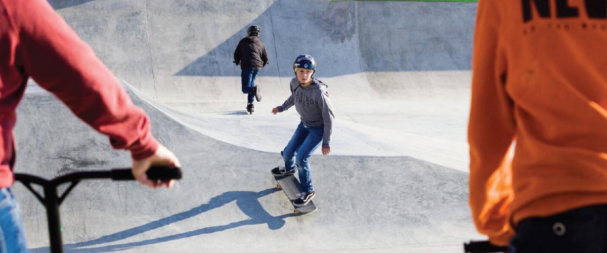 Ungdom på rullebrett og sparkesykkel i rullepark