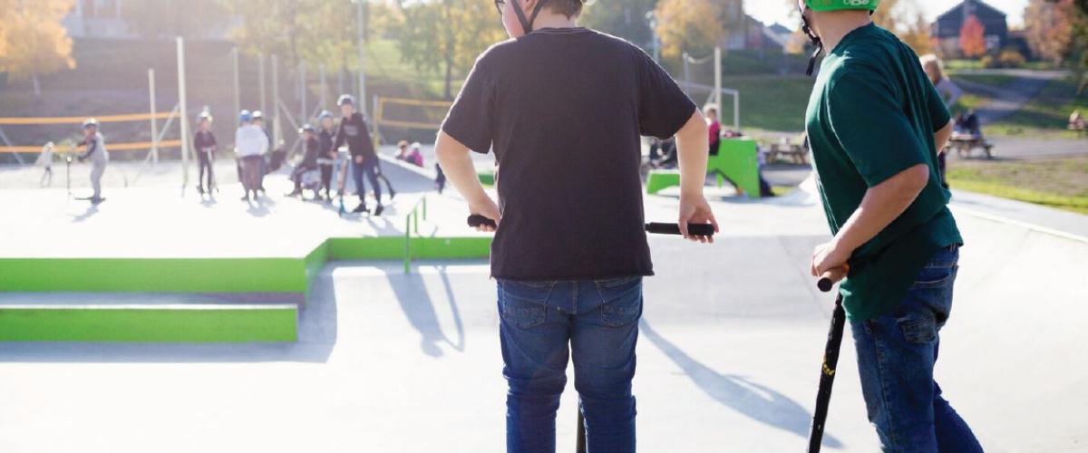 To gutter med sparkesykkel og hjelm på rullepark, sandbaner i bakgrunn