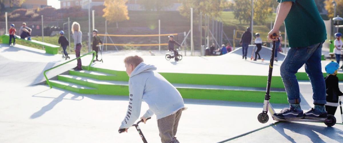 Ungdom på sparkesykler i rullepark med sandbaner i bakgrunn