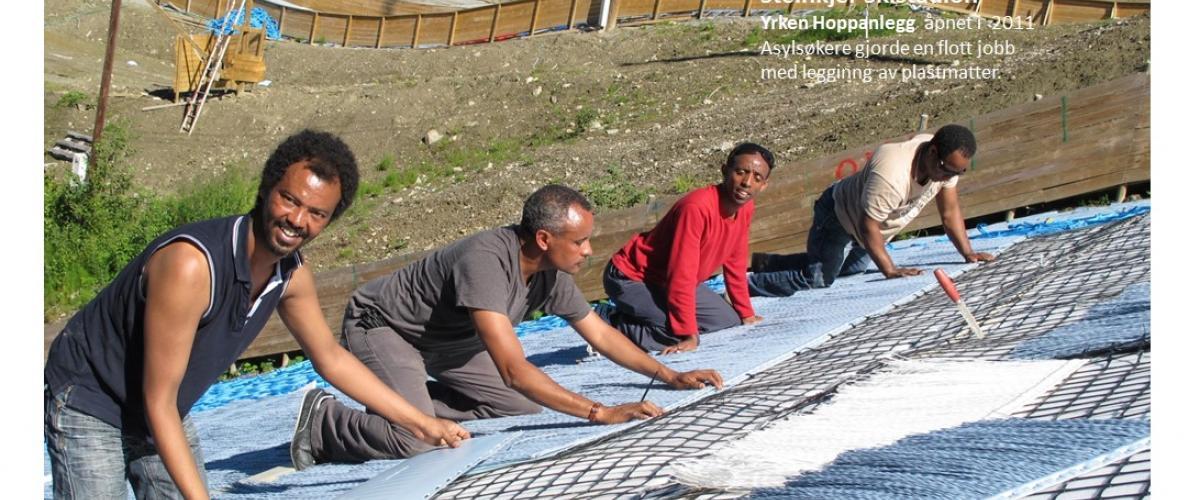 Asylsøkere gjorde en glott jobb med legging av plastmatter ved bygging av hoppanlegget.