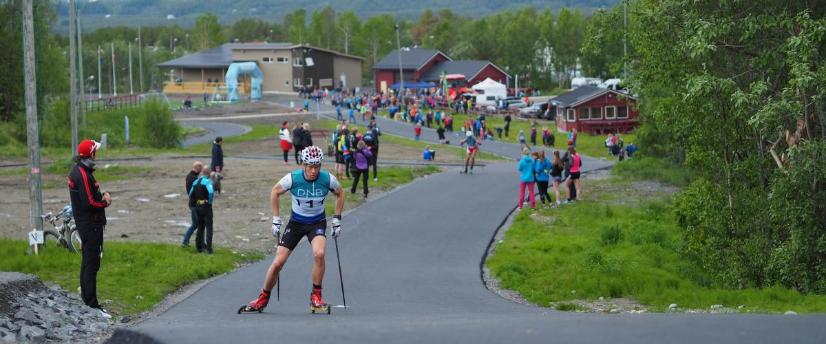 Skiløper på vei opp bakke på asfaltert rulleskiløype