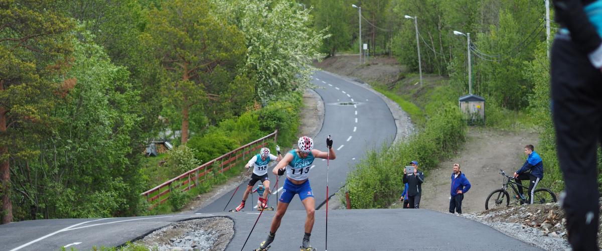To rulleskiløpere på vei opp bakkene