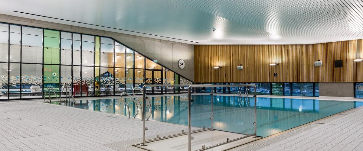 Innsiden av svømmehallen med fliser, basseng og vinduer.