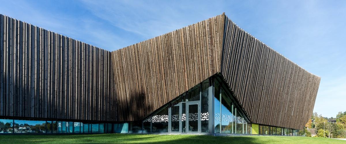 Utsiden av bygg med vindusfronter og treverk i overkant.