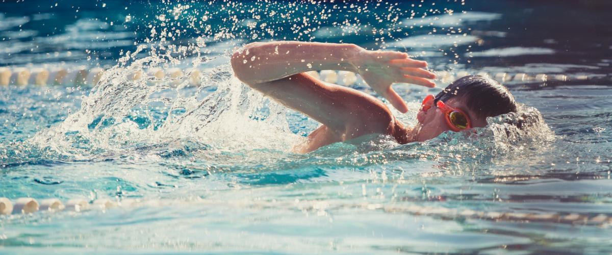 Ung svømmer tar svømmetak i basseng