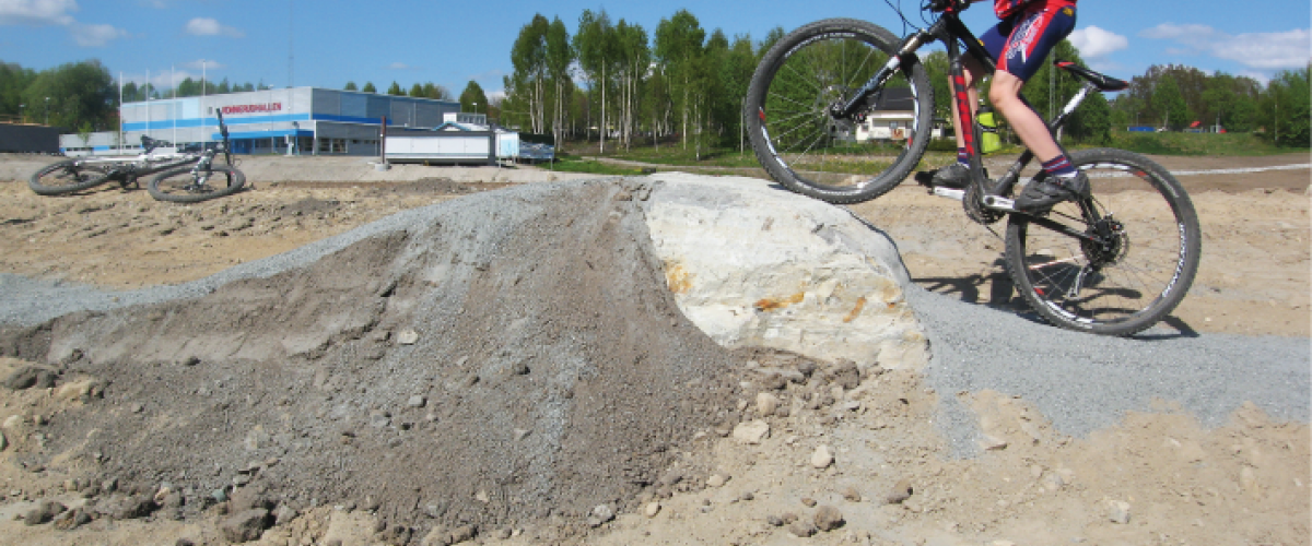 Syklist som forserer et hinder av stein og grus