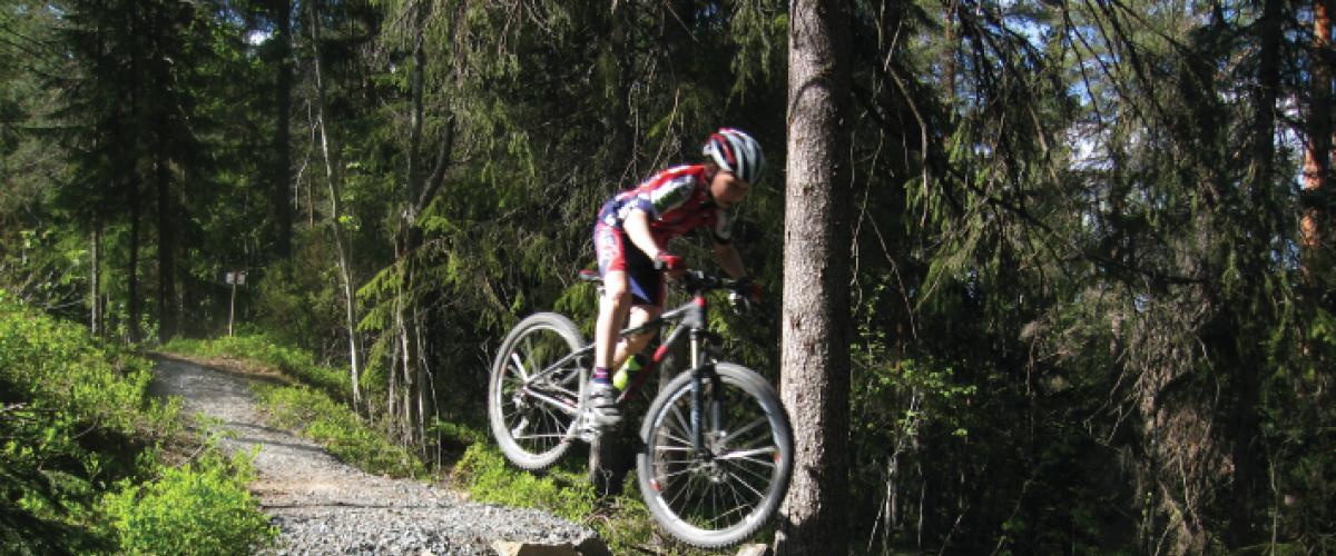 Syklist hopper i skogen