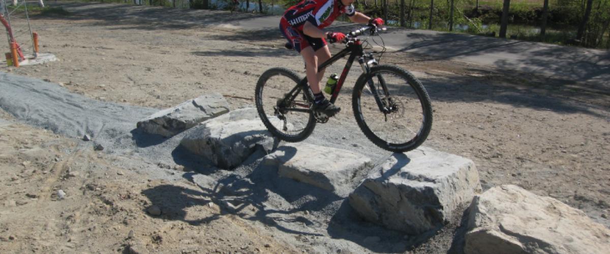 Syklist som sykler over små stenblokk
