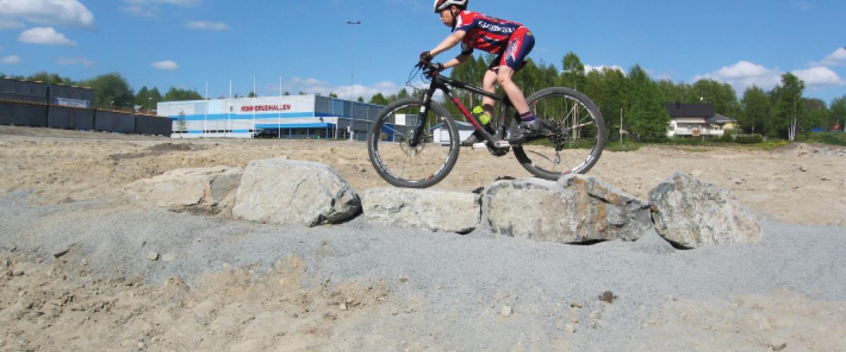 Syklist som sykler over små steinblokk