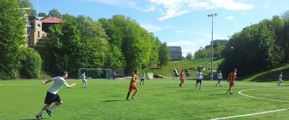 To lag spiller fotballkamp på kunstgressbane