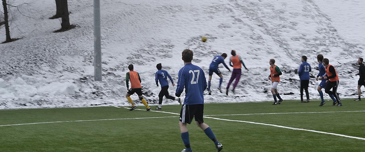 To lag spiller fotballkamp på kunstgressbane på vinterstid