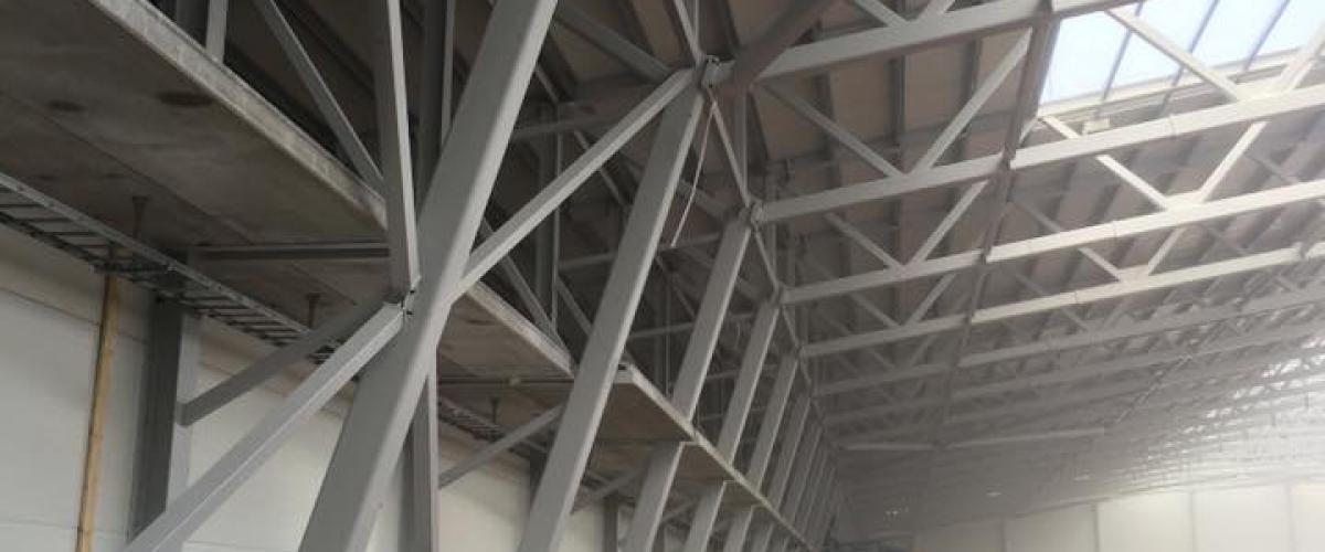 Oppføring av fotballhall, vegg og bjelker uten tak.