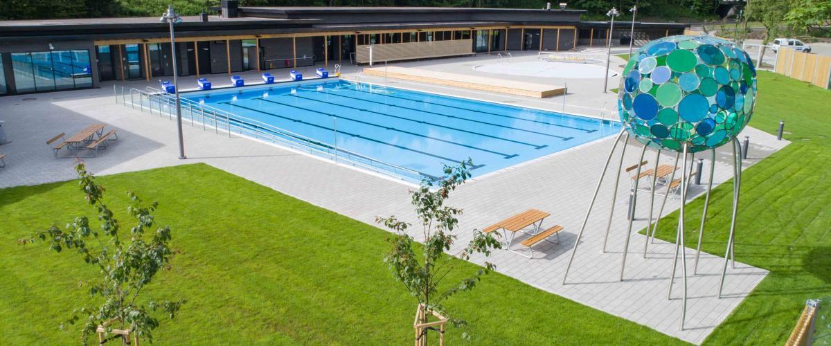 Utendørs svømmebasseng med grøntområder