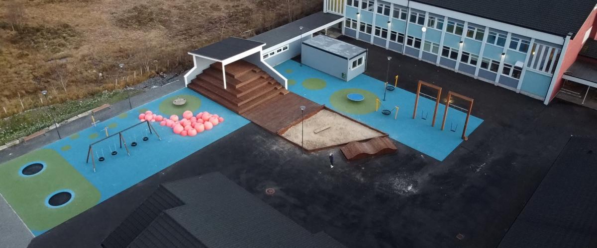 Oversikt over aktivitetspark med disser, trampoliner, sandkasse og amfi.