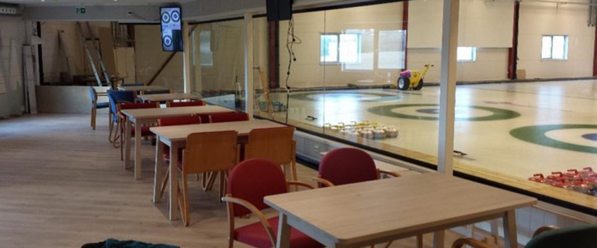 Sosial sone med bord og stoler. Innsyn til curlinghallen.