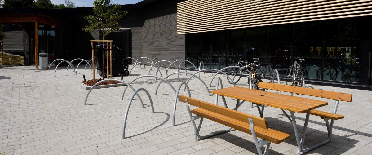 Utside av svømmeanlegg med benk og sykkelparkering