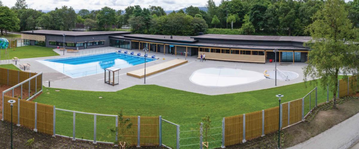 Utendørs inngjerdet svømmeanlegg med grøntområder