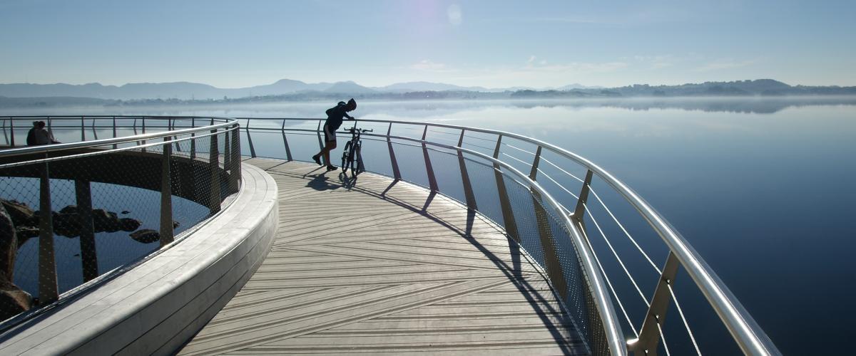 Syklist hviler på bro med fjordutsikt