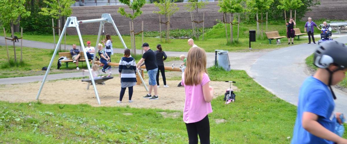 Huskestativ i parken, mange barn og voksne i parken.