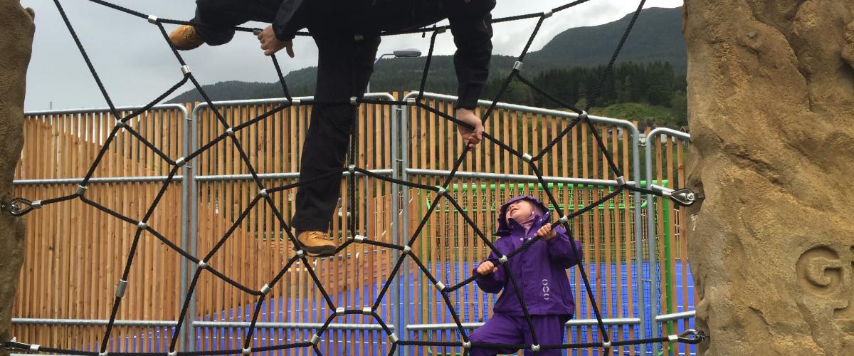 Barn med voksen som klatrer i eit nett
