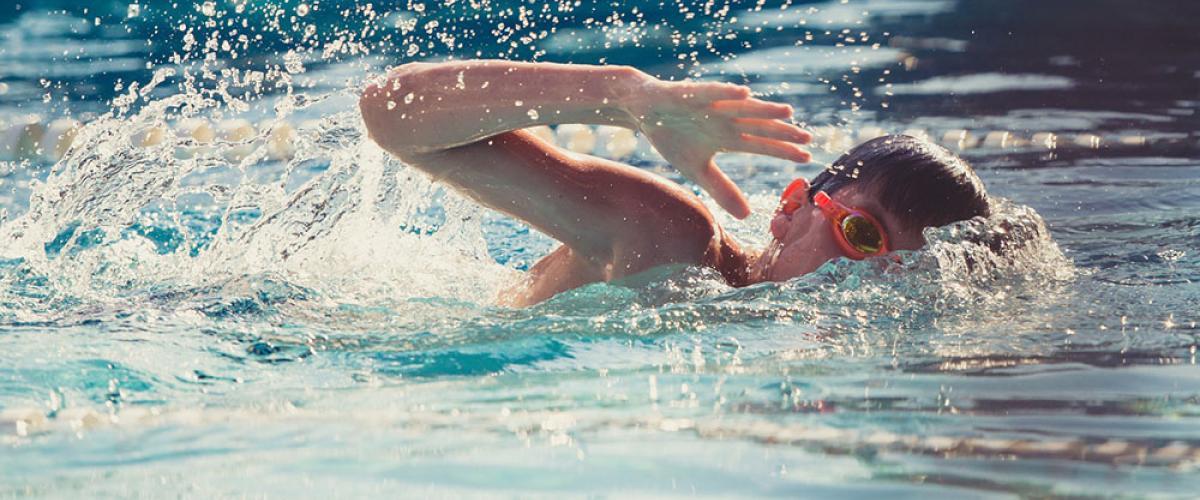 Ung gutt tar svømmetak i basseng