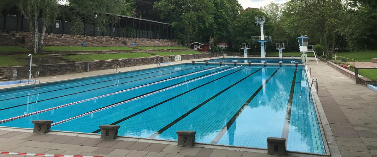 Utendørs svømmebasseng, med hoppetårn og grøntområder.