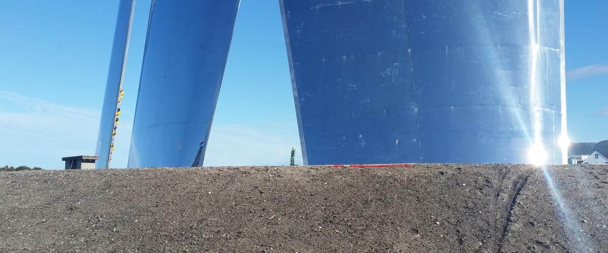 Tre skrå seil av betong og plankpolert stål med klatretak