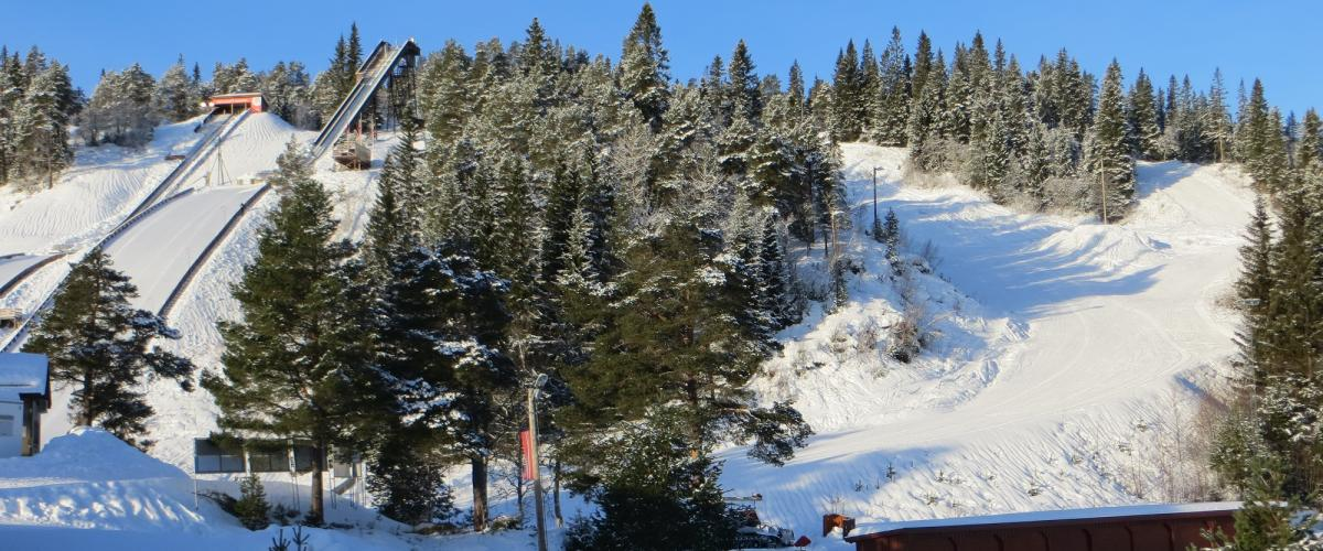 Smal alpinbakke kommer ned på siden av hoppbakkene