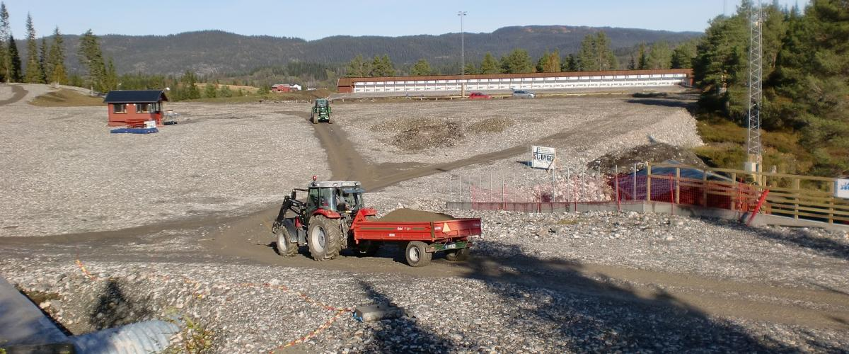 Traktorer kjører stein og grus ut på skistadion