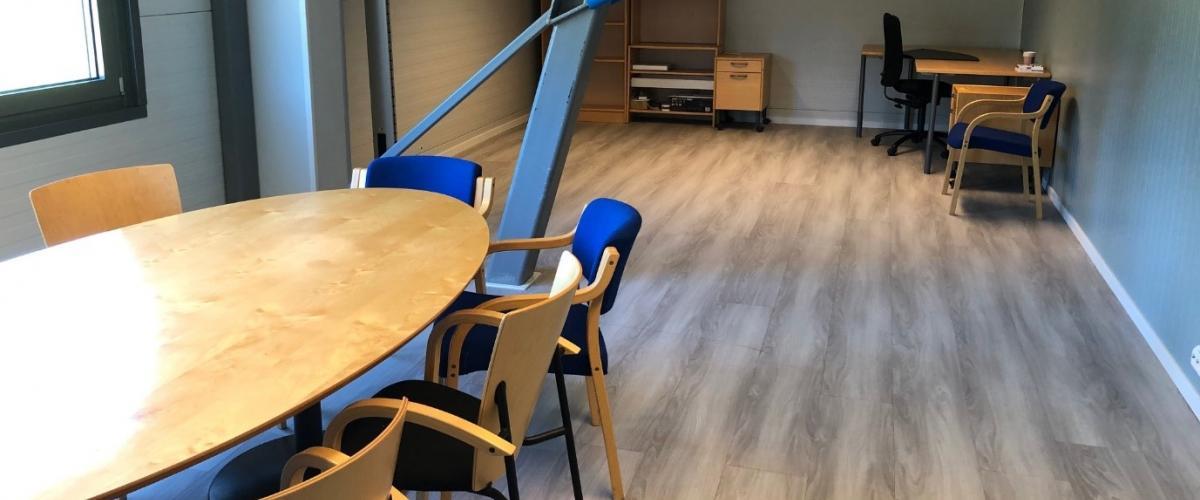 Et rom med konferansebord og stoler.