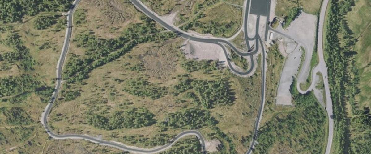 Flyfoto av skistadion med rulleskiløypa, stadionhus, parkeringsplass og innkjøring frå E39