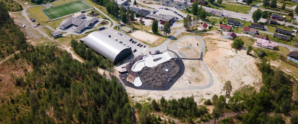 Skole, hall og aktivitetspark sett fra lufta.