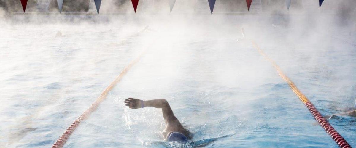 Svømmer tar svømmetak i utendørs svømmebasseng