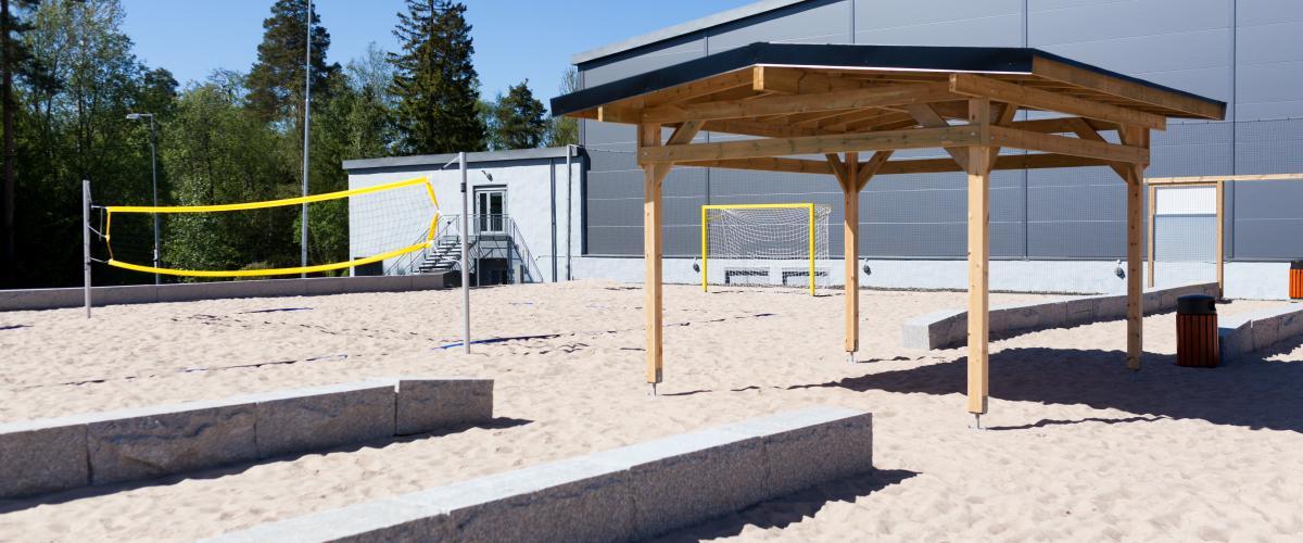 Benker og tak over hode mellom de to beachhåndballbanene