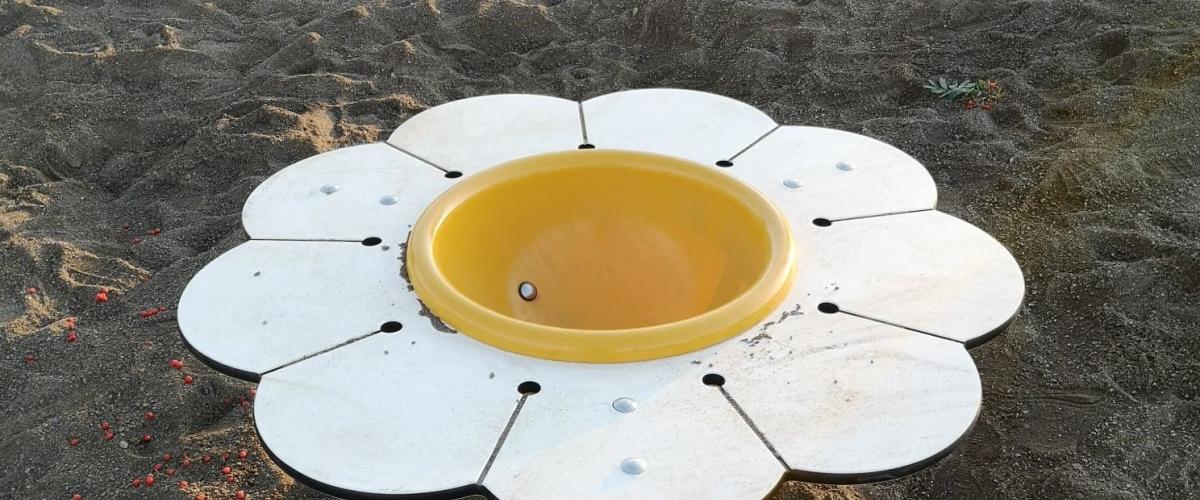 Vannbord utformet som en blomst plassert i sandkasse
