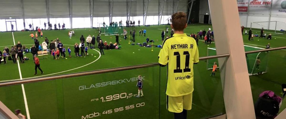 Gutt som ser ned på fotballbanen i Vestfoldhallen.
