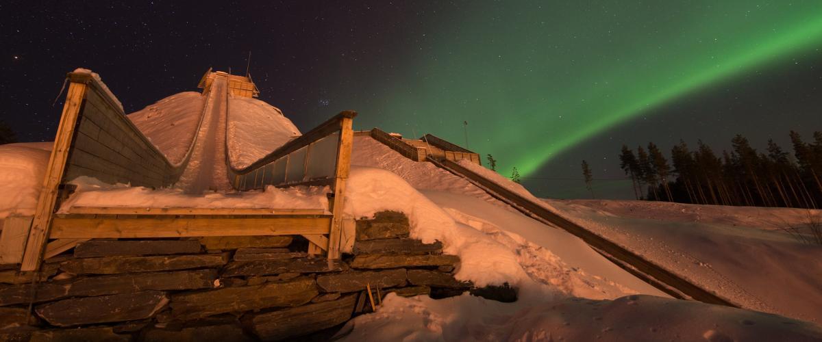 Hoppbakke badet i grønt nordlys